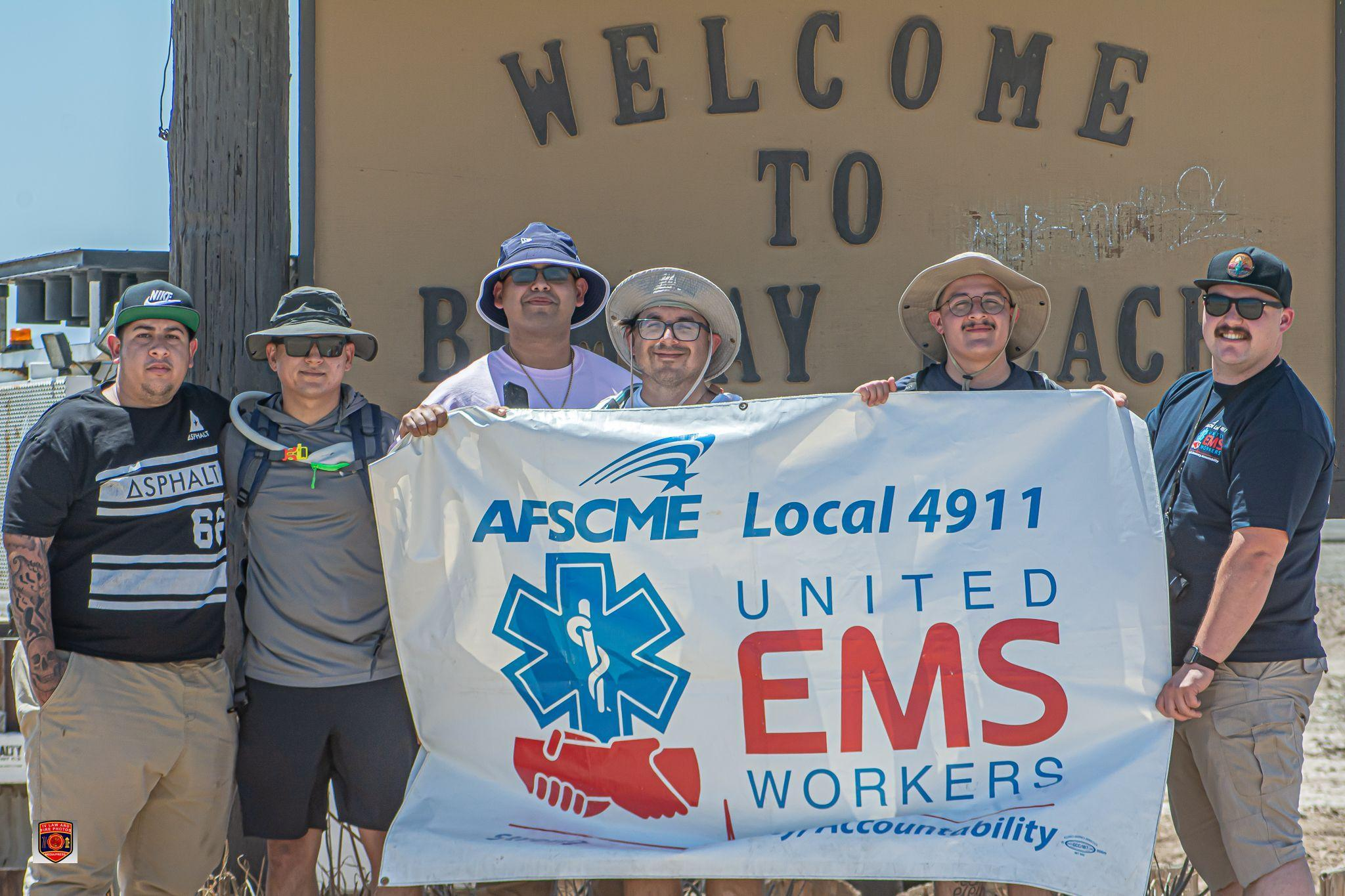 Guillermo and co-workers hold AFSCME Local 4911 banner